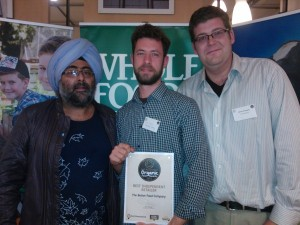 Shop Supervisor Ian Cross and Assistant Manager Edward Temple receiving the award with broadcaster Hardeep Singh Kohli.